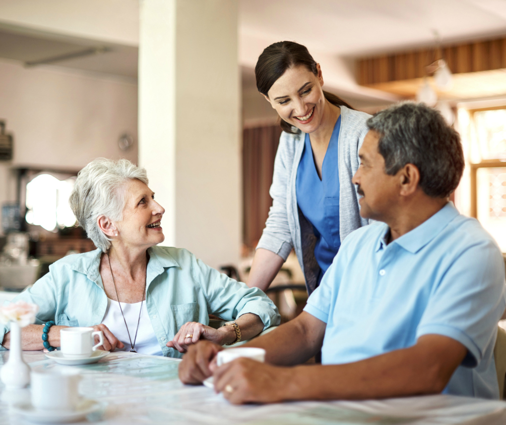 Two nursing-home residents, a woman and a man, talk with a female staff member.