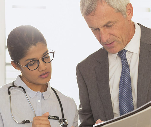 Doctor and executive reviewing information on a tablet computer.