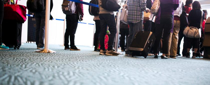 Passengers stand in an airport security screening line.