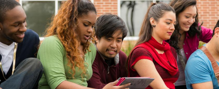 A group of young adults hanging out with laptops and tablets outdoors.
