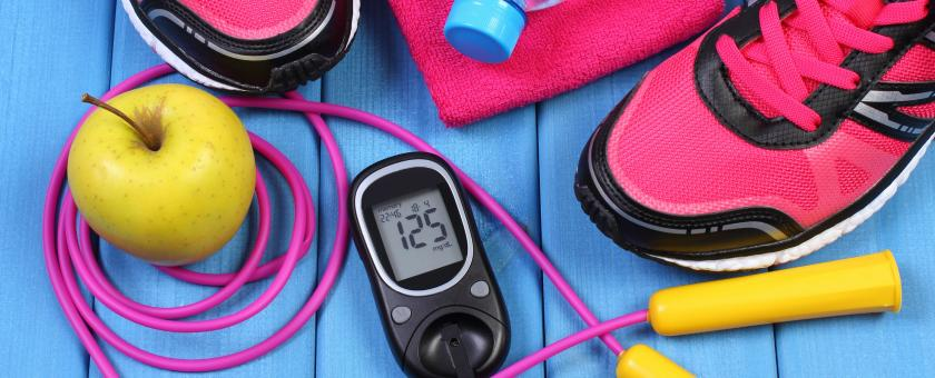 An arrangement of fitness equipment, a blood-sugar monitor, and healthy snacks.