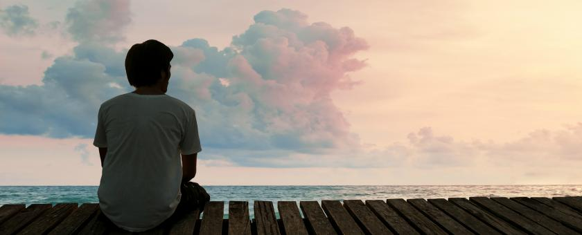 A solitary man watches the sun rise over the ocean from a pier.