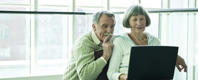 older couple looking at information on a laptop