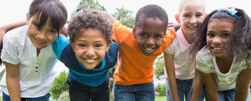 A diverse group of children link arms while playing outside.