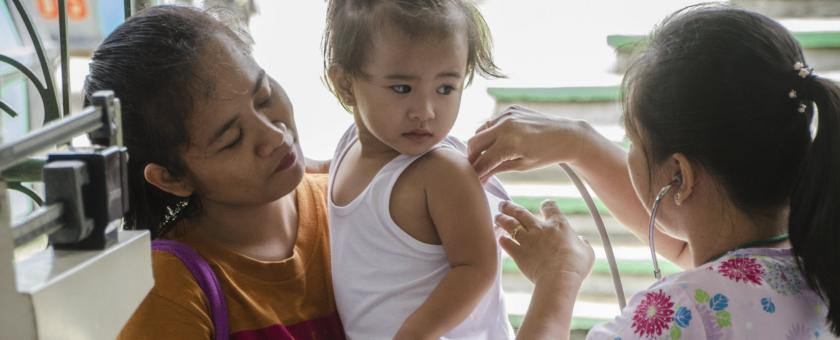 Filipino doctor measures a young patient