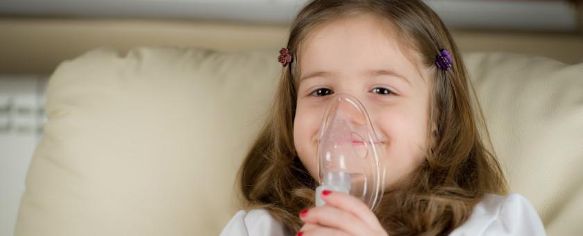 A young girl uses an inhaler