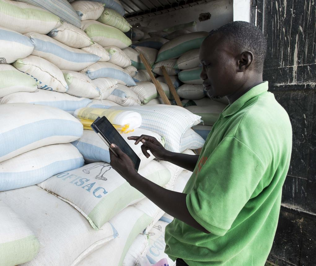 A technician checks the stock with a tablet at Aïssatou GAYE's mini rice company in Richard Toll town, Senegal. Photo by Xaume Olleros / RTI
