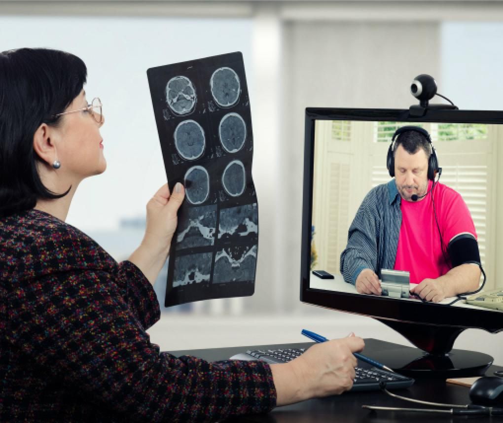 A female doctor and a male patient review x-rays via videoconference.