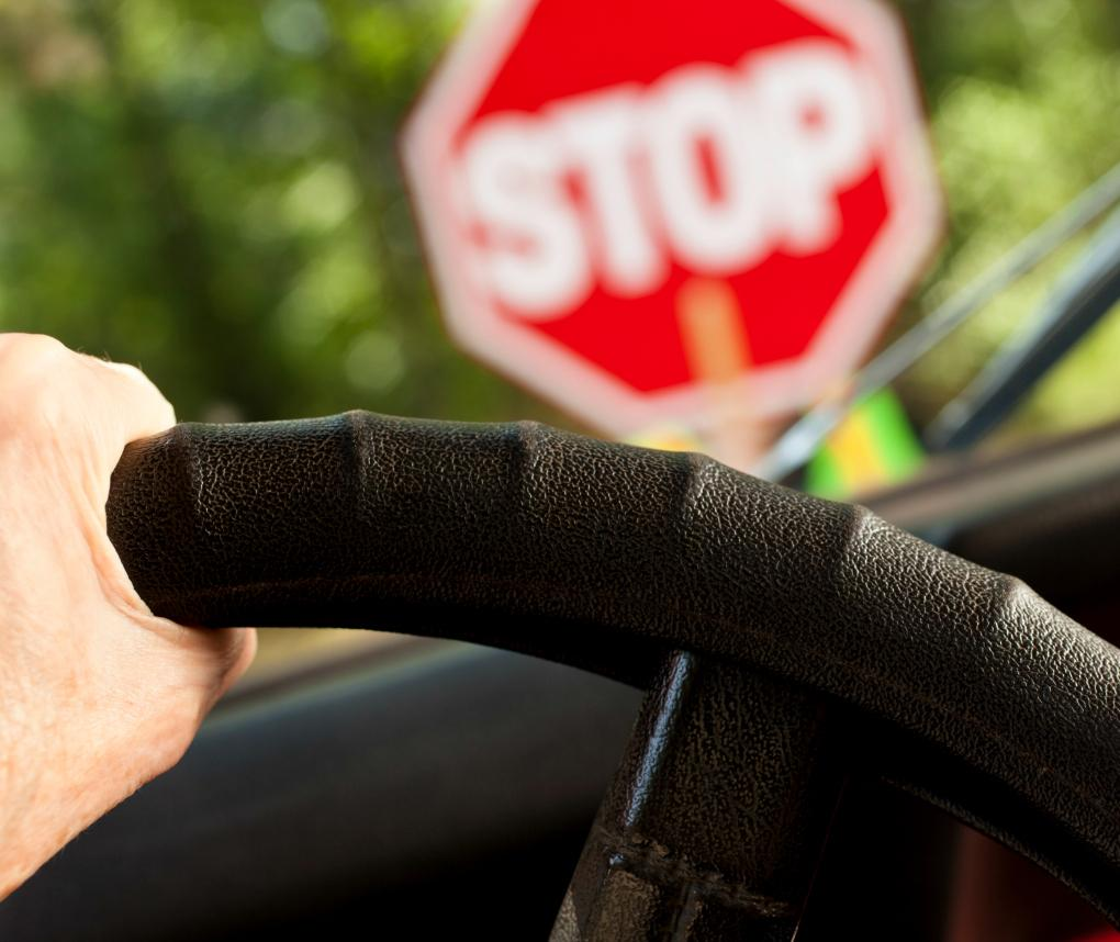 A stop sign is visible through the windshield of a car, over a closeup of a hand on a steering wheel.
