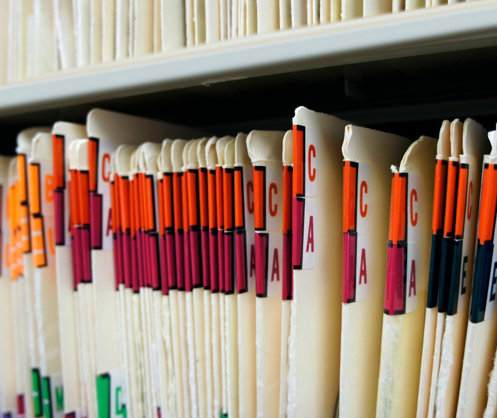 A row of alphabetized medical records on a shelf