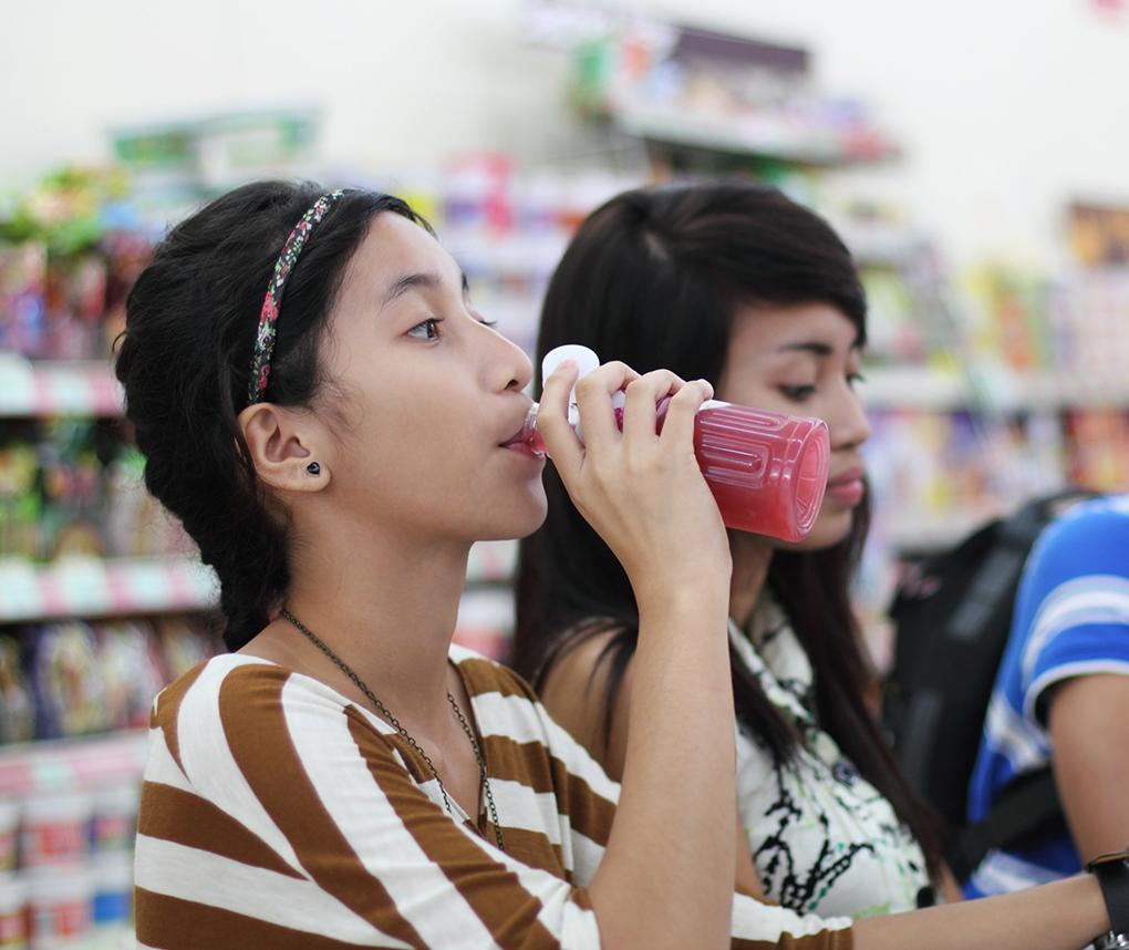 Asian teenagers drink sodas at an outdoor cafe.