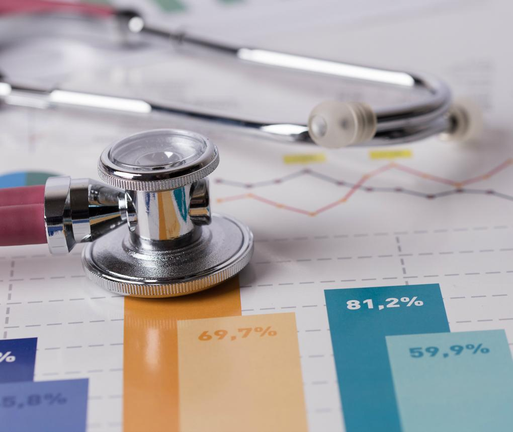An array of items related to health care finance, including a stethoscope, tablet, and charts showing percentages.