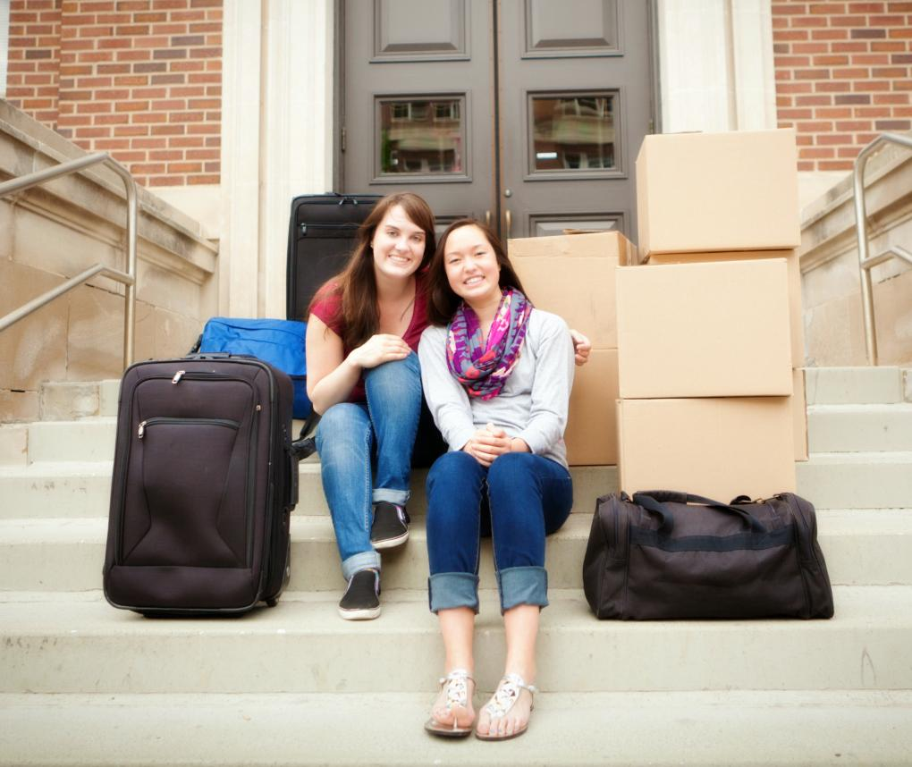 Two women sit with luggage on the steps of a college dorm.