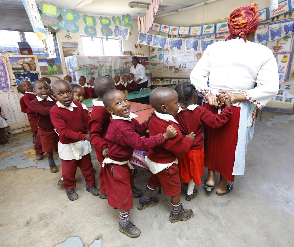 Children in a brightly decorated early-childhood classroom in Kenya form a chain and walk in a circle with their teachers.