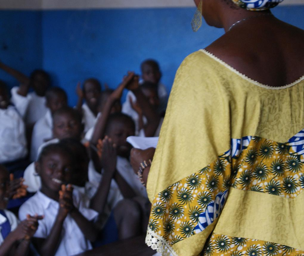 A female teacher works with a classroom of primary-school students in Liberia.