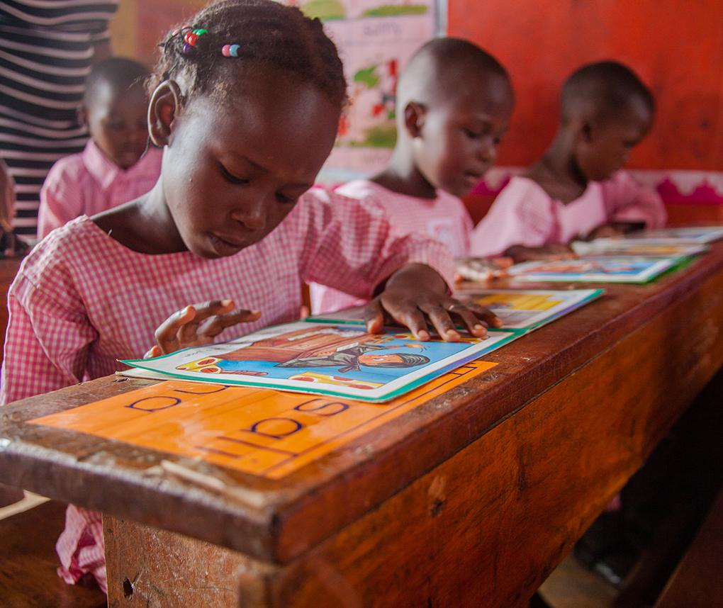 Ugandan schoolchildren practice reading in a classroom.