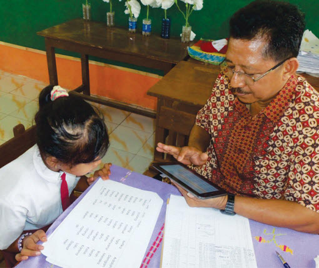 Teacher evaluates the reading ability of a student in Indonesia
