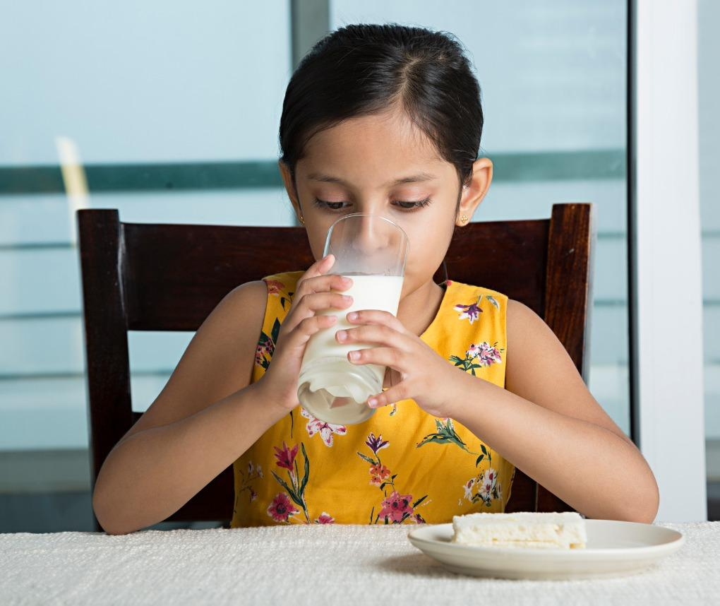 A young girl is drinking a glass of milk