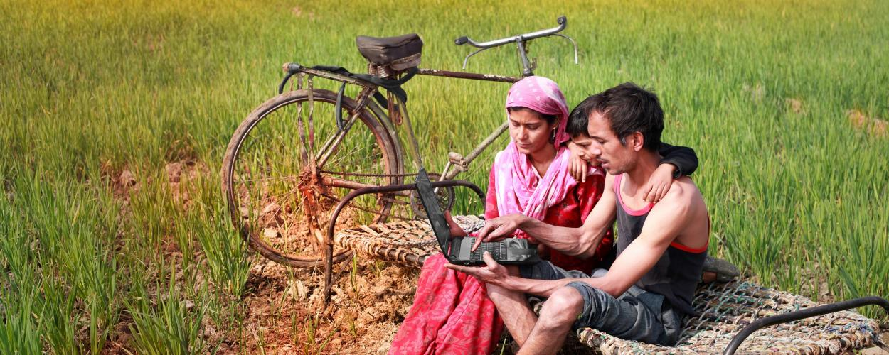 A family uses a laptop in a field