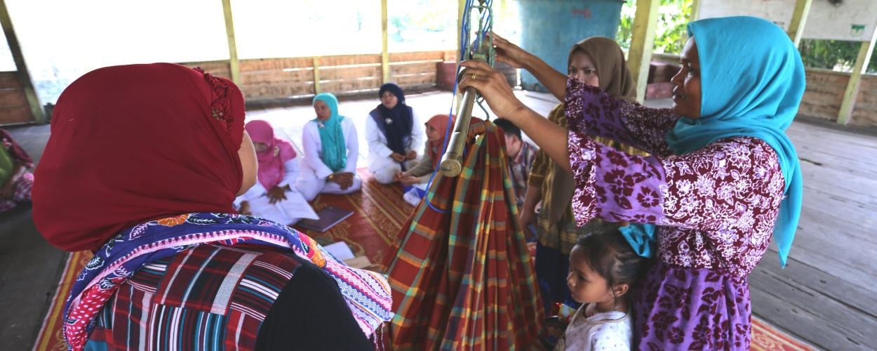 Health workers in Aceh Singkil weigh babies