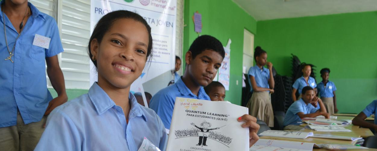 A teenage girl shows her work in an Alerta Joven academic program in the Dominican Republic.