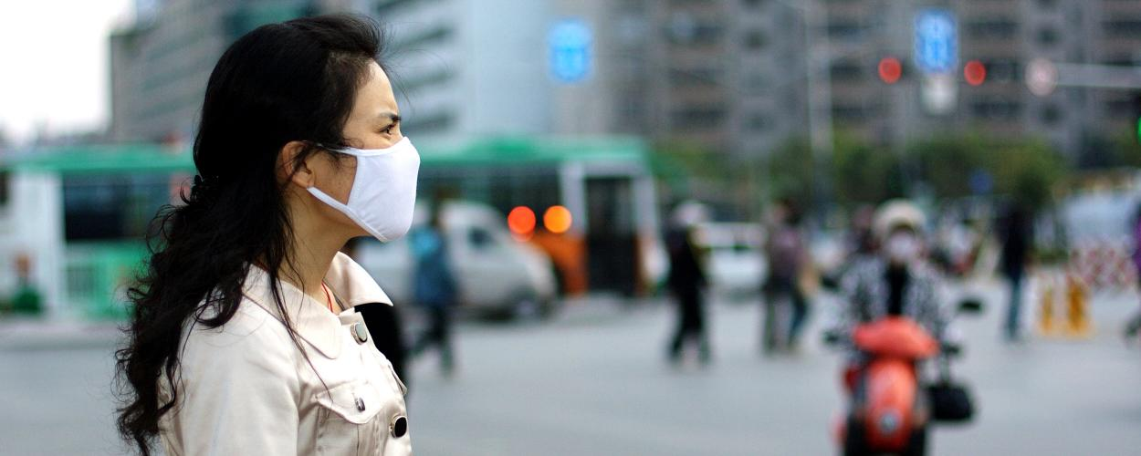 woman wearing a breathing mask on a city street in China