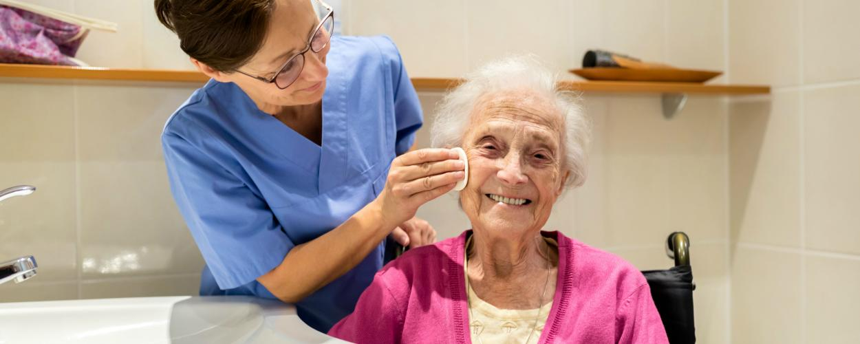 A female caregiver helps an elderly patient wash her face by a bathroom sink.