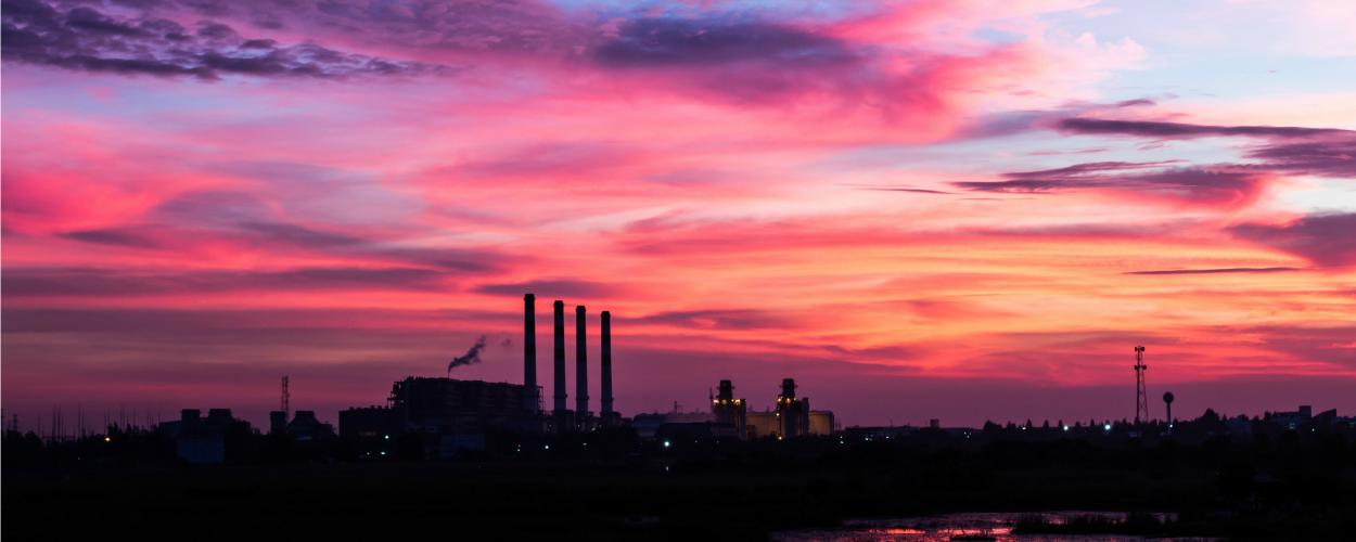 A landscape at sunset with a factory