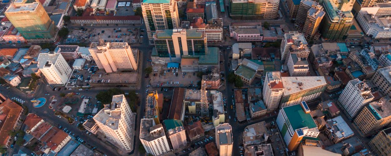 An aerial view of Dar es Salaam, Tanzania, shows busy streets and high-rise buildings.