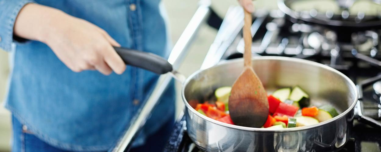 A woman cooks vegetables on a stovetop