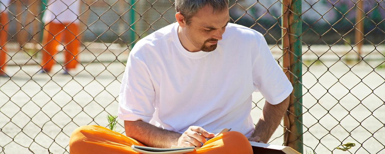 A man does schoolwork in an outdoor prison yard