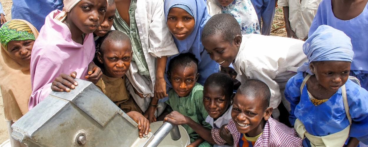 Children gather around new water borehole in Nigeria