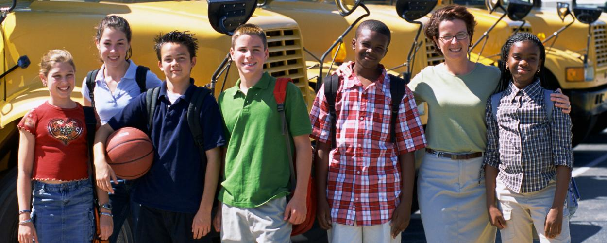 A group of middle-school students and a teacher smile while standing in front of a row of yellow school buses.