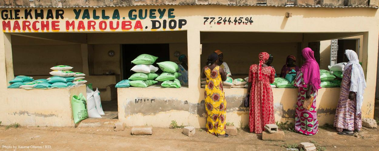 Women buy and sell rice at a market in Senegal.