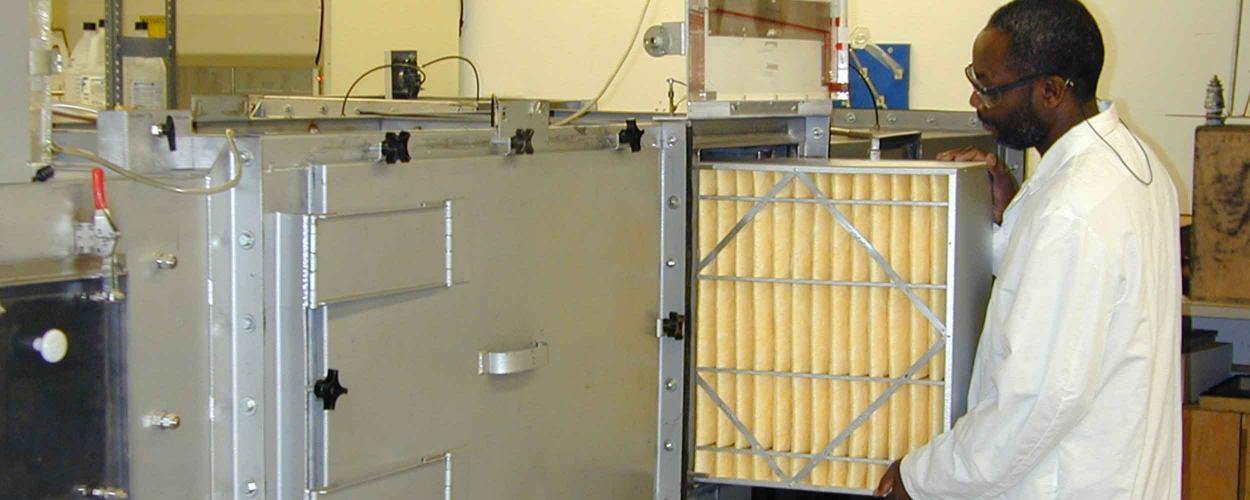 technician loads an air filter in RTI's test rig