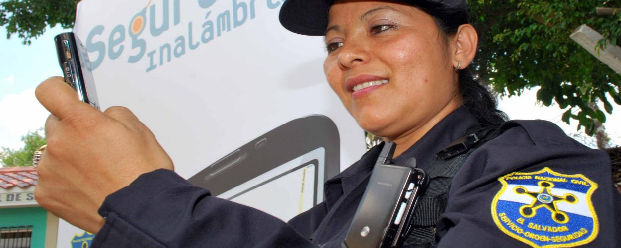 A Salvadoran law enforcement officer uses a mobile phone to report an incident