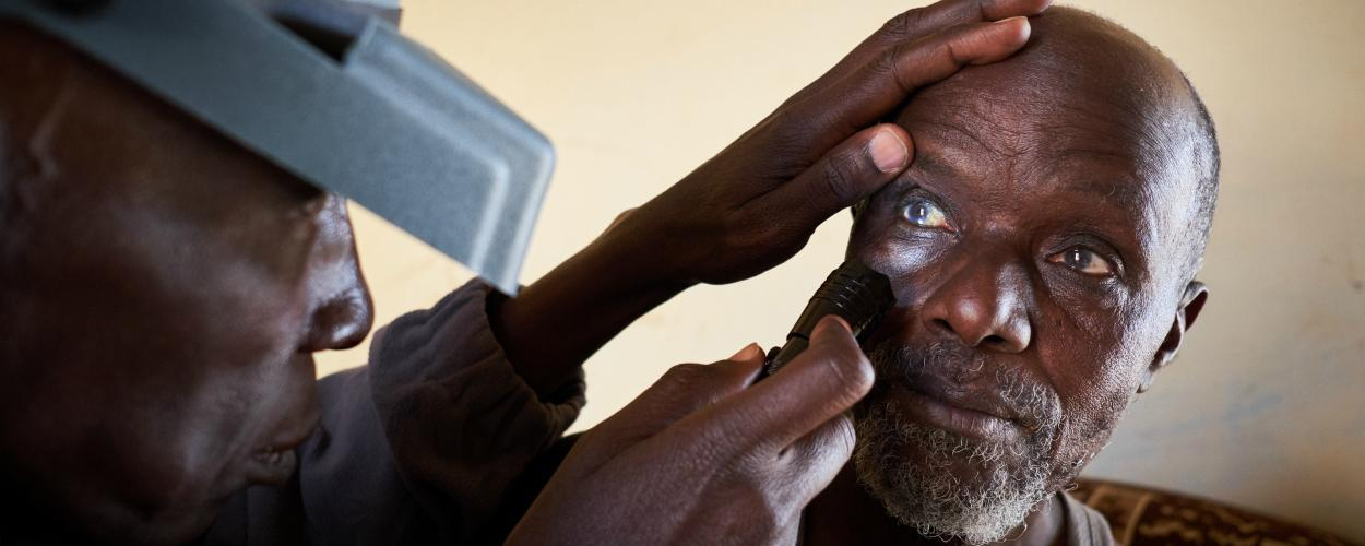 A health worker checks a man's eyes for signs of trachoma.