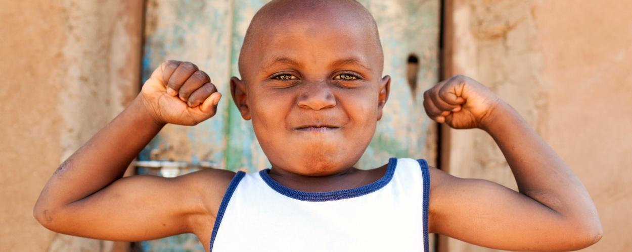 Tanzanian boy flexing his muscles