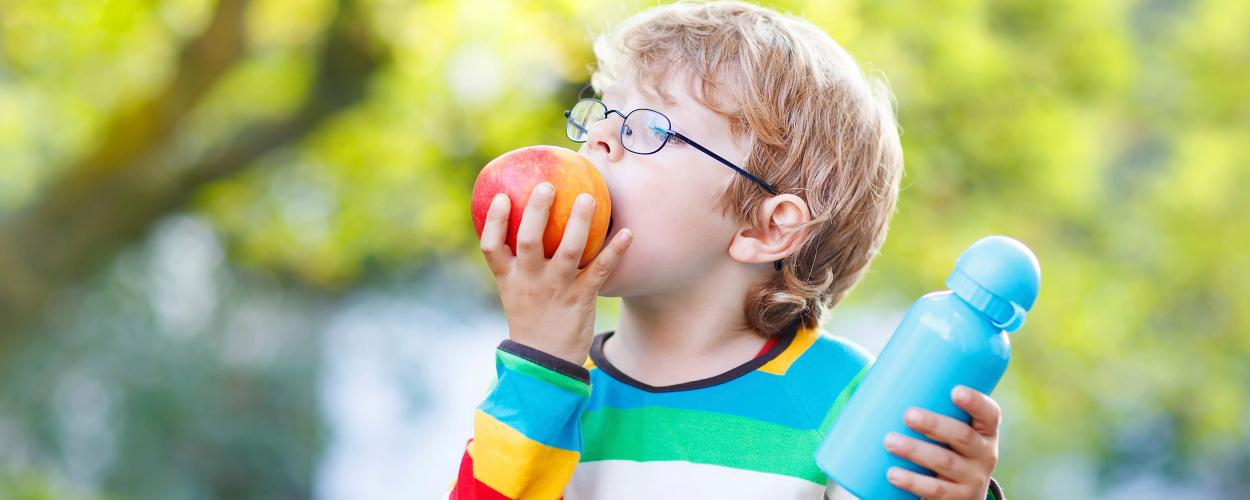 A boy eating an apple and holding a water bottle