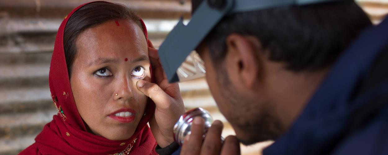 A health worker checks a woman's eyes for signs of trachoma.
