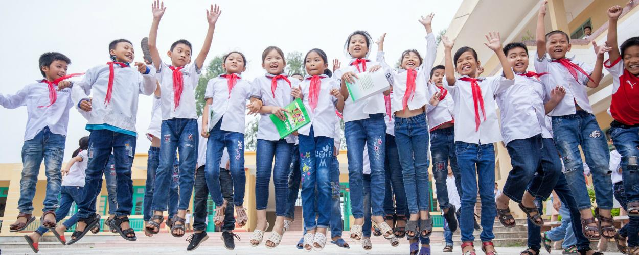 Schoolchildren in Vietnam hold hands, smile, and jump.