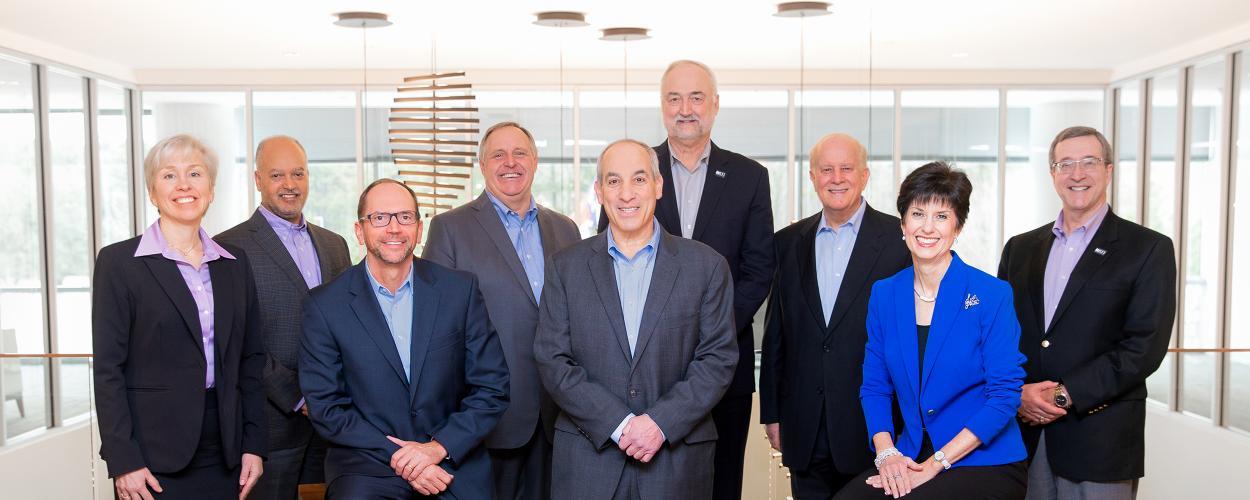 A group photo of RTI's Executive Leadership Team. From left: Lisa May, Paul Weisenfeld, Mike Kaelin, Tim Gabel, Allen Mangel, E. Wayne Holden, James Gibson, Teena Piccione, G. Edward Story