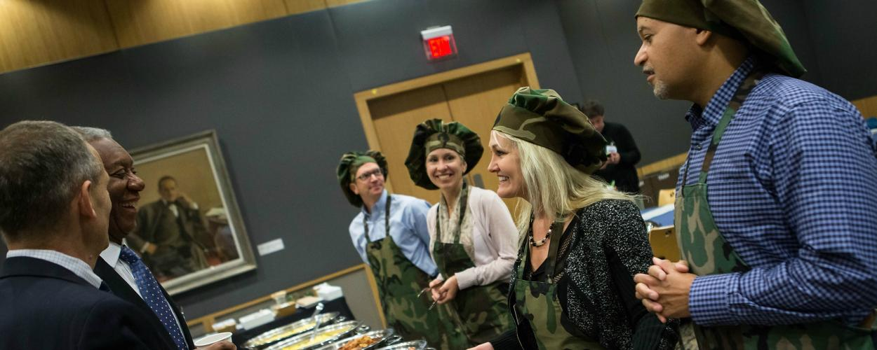 Executives prepare to serve employees at the annual veterans' breakfast