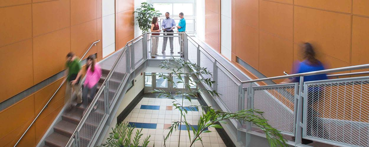 Staff members move through the lobby of the Johnson Science and Engineering Building on the RTP Campus