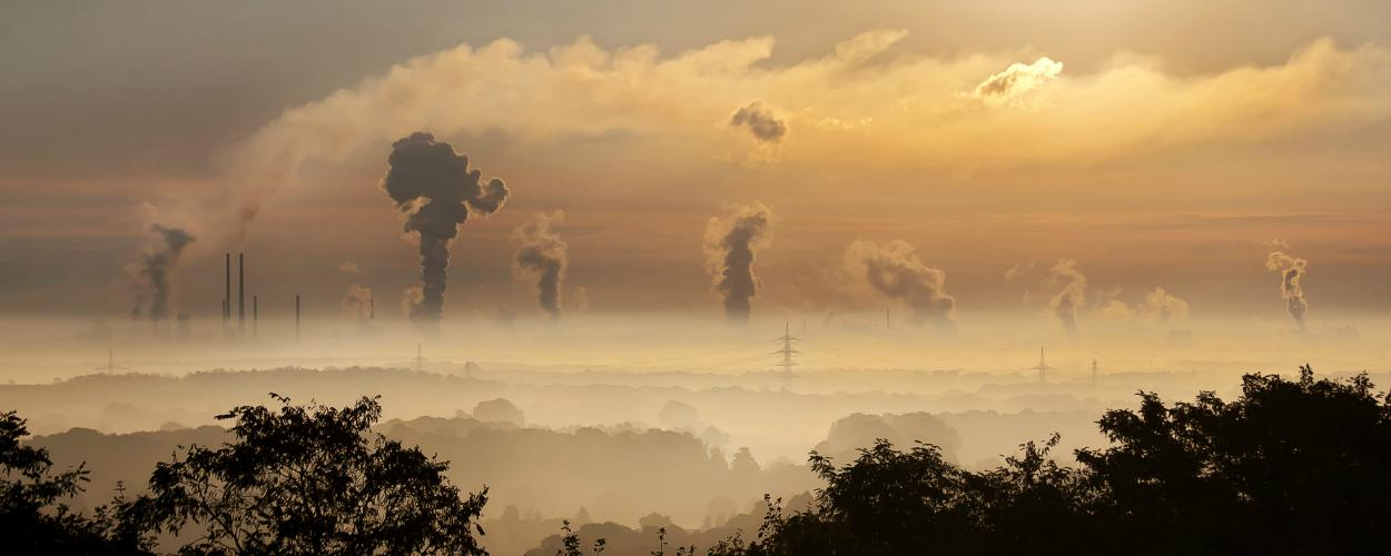 The sun rises over a landscape with factories and smokestacks.