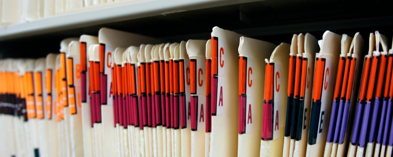 A row of alphabetized medical records on a shelf