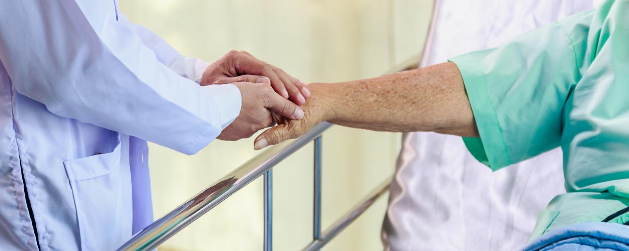 In a hospital room, a doctor holds a patient's hand.