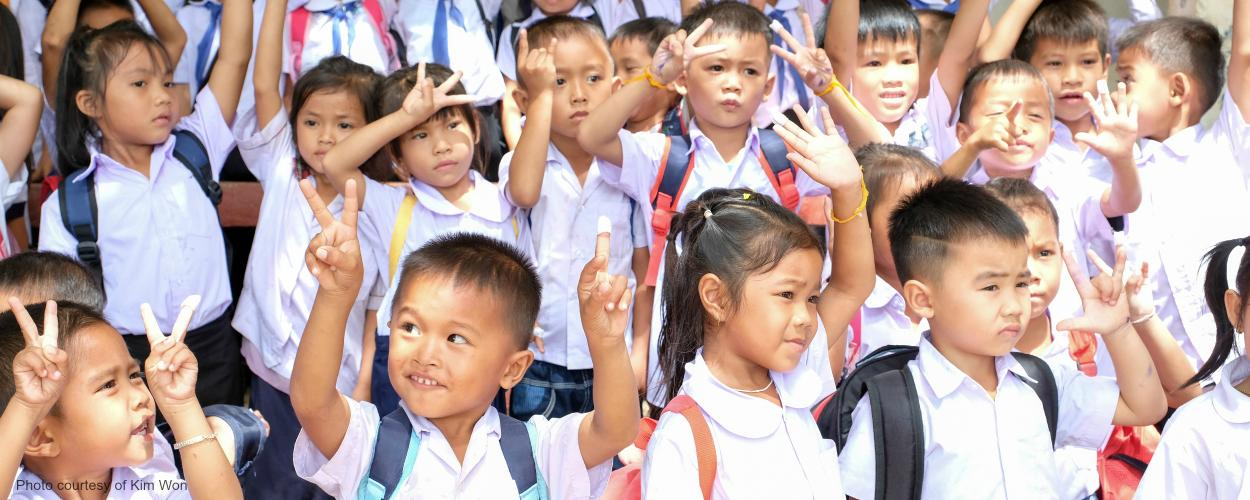 Schoolchildren in Laos raise their hands.