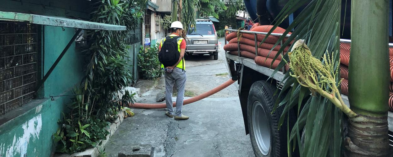 A sanitation worker services a building in Manila, Philippines.