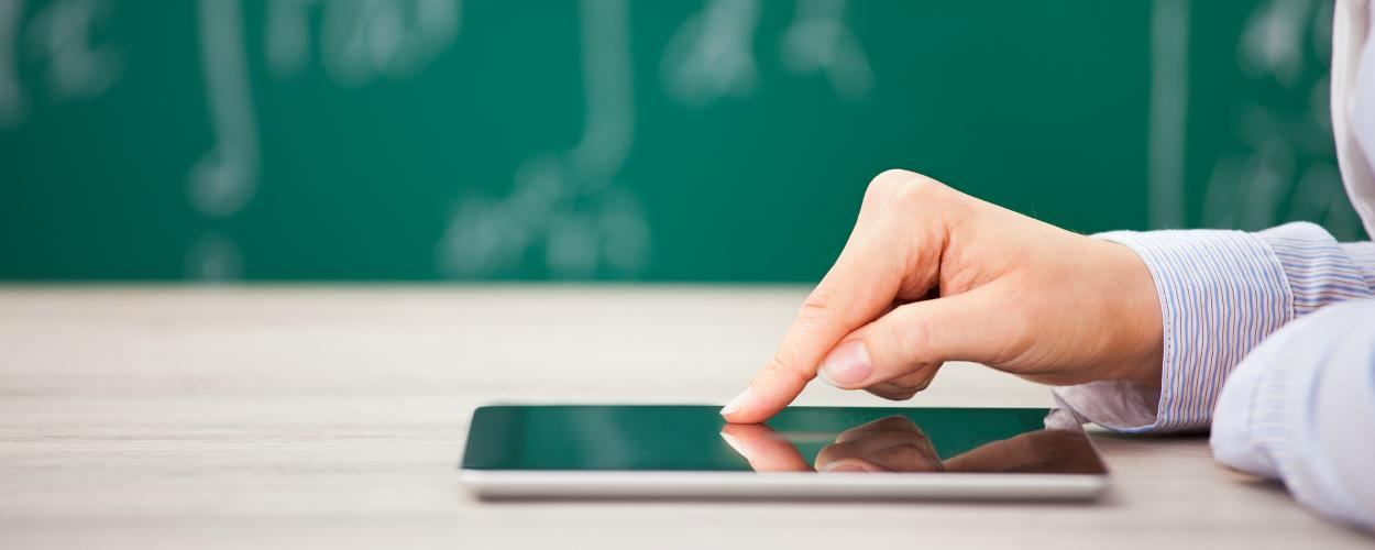 A person uses a tablet in front of a chalkboard in a classroom